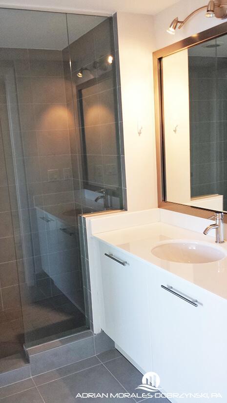 Shower with glass door in 1 bedroom at Mint condo